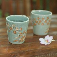 Celadon ceramic coffee mugs, 'Golden Orchid' (pair)